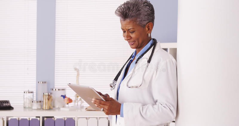 Happy Black Senior doctor standing in office with tablet stock photography