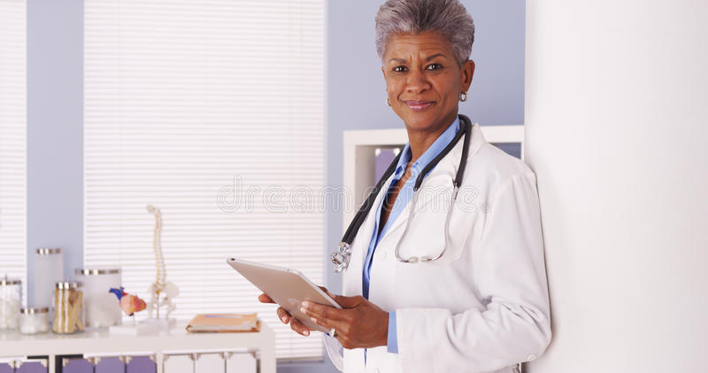 Happy Black Senior doctor standing in office with tablet stock photos