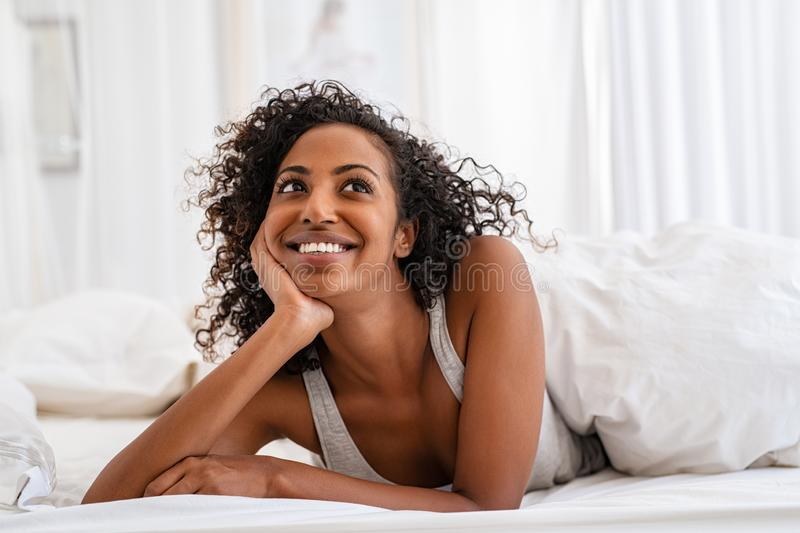 Happy black woman in bed thinking royalty free stock images