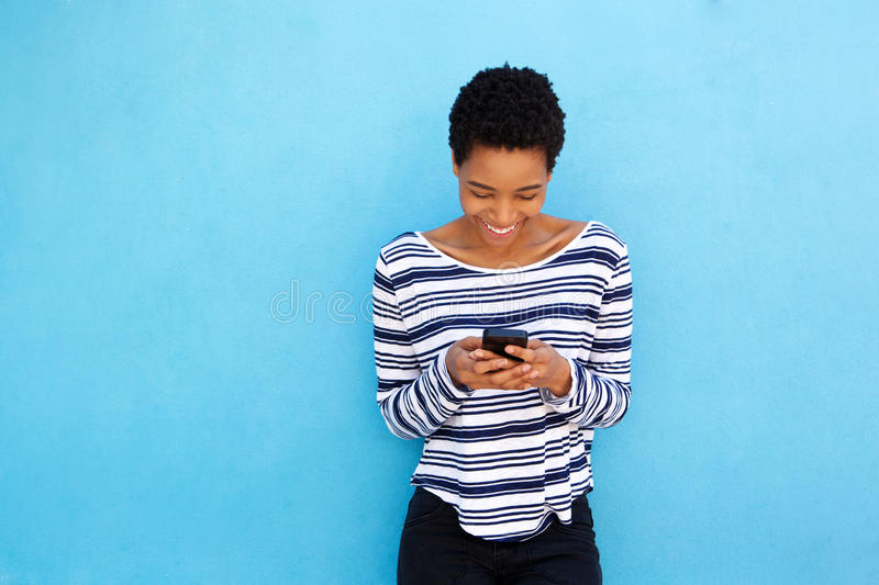 Happy black woman looking at mobile phone by blue background stock photos