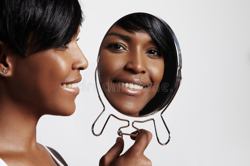 Happy black woman with mirror. Black woman with a mirror showing at her ideal skinr royalty free stock images