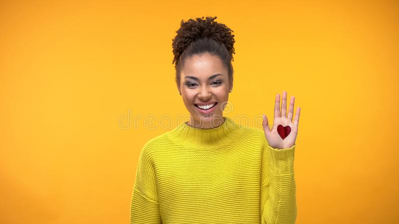 Happy black woman showing open palm with heart sign, sincere love, relationships royalty free stock photo