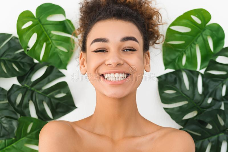 Happy black woman smiling against tropical leaves stock photo