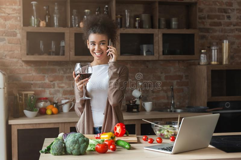 Happy black woman talking on smartphone in kitchen royalty free stock photography