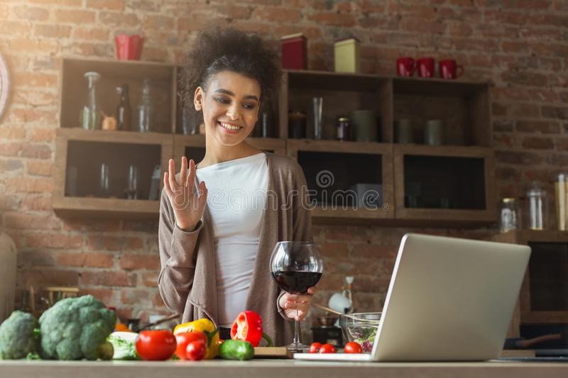 Happy black woman using laptop in modern kitchen interior royalty free stock images