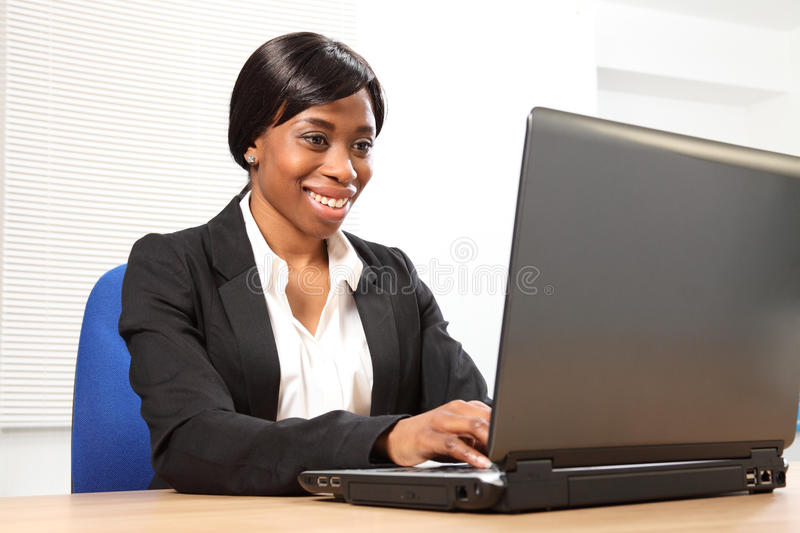 Happy black woman using laptop at office desk. Happy young black woman working in office sitting to her desk using her laptop, with a beautiful smile. Picture stock images