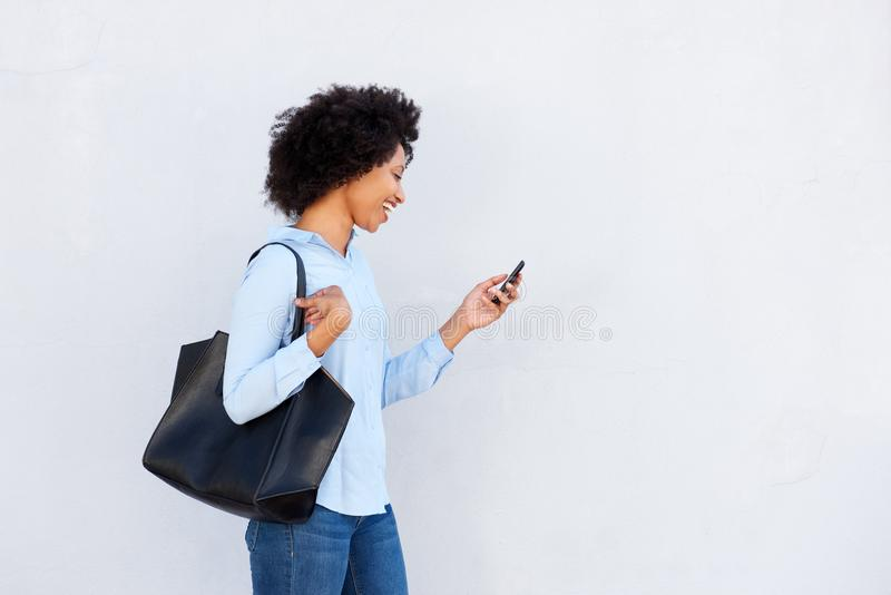 Happy black woman walking with mobile phone and purse on gray background royalty free stock photos