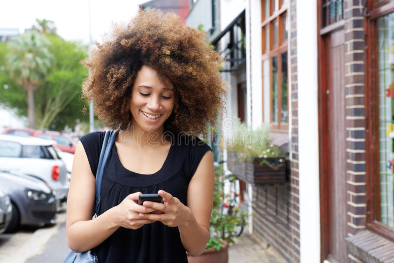 Happy black woman walking and reading text message stock photo