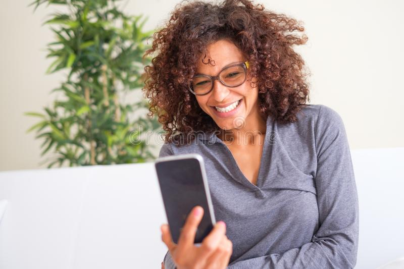Happy black woman watching cellular display stock photography