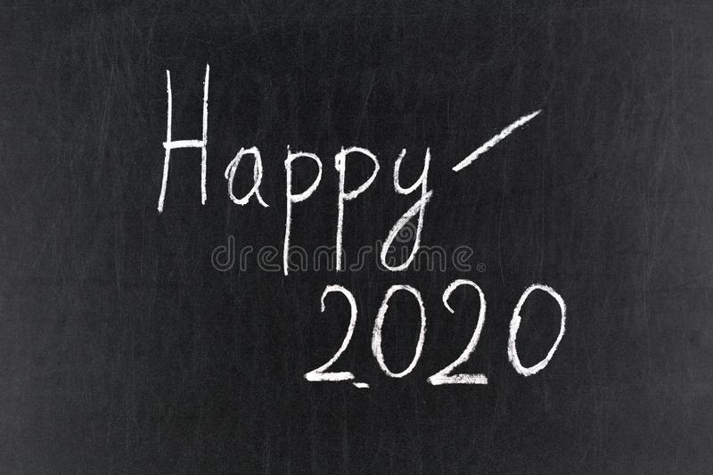 Happy 2020 blackboard with an hand writing stock image