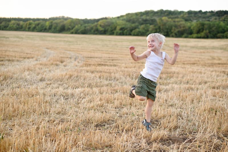 Happy blond boy is dancing on a mown wheat field. Sunset time royalty free stock image