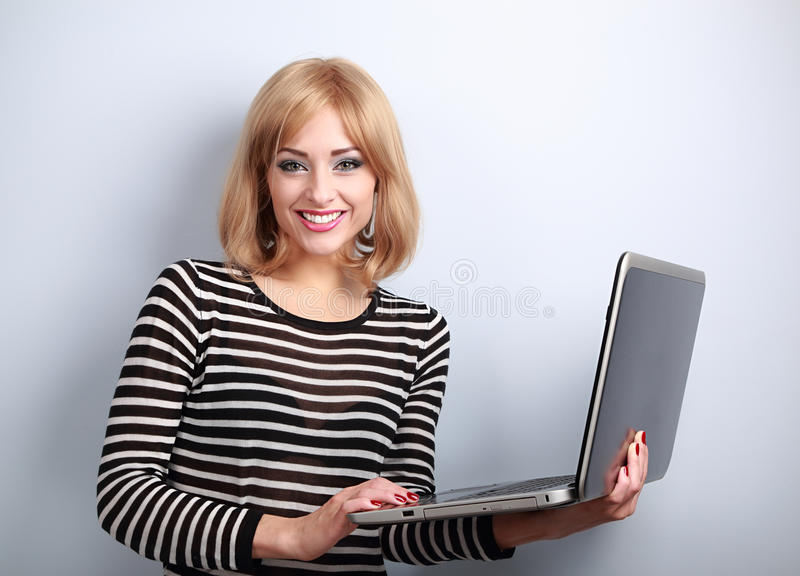 Happy blond casual woman holding laptop in hand and toothy smiling. On blue background stock photos