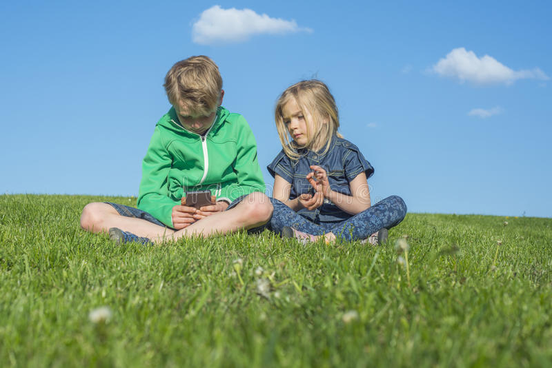 Happy blond children using smartphone (watching movie or playing game) sitting on the grass. stock photos