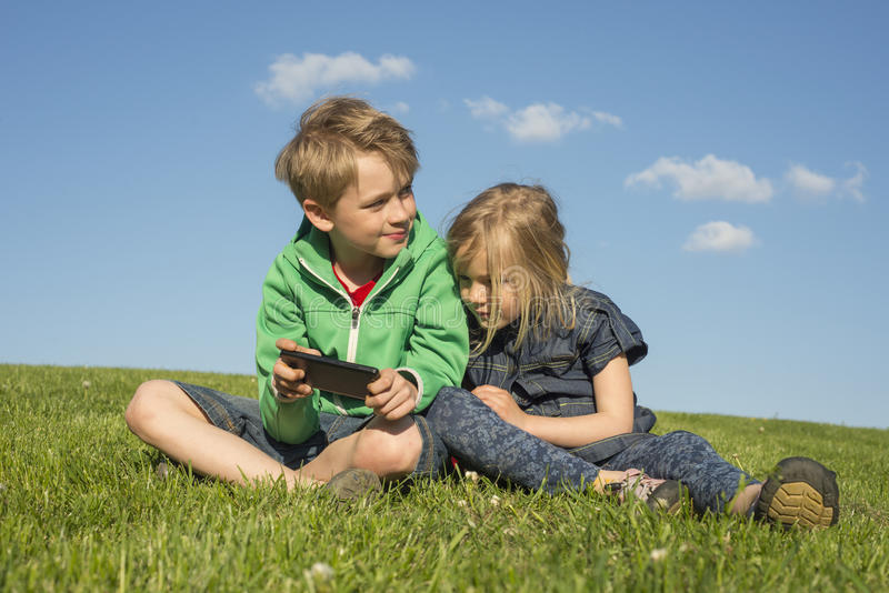 Happy blond children using smartphone (watching movie or playing game) sitting on the grass. royalty free stock photography