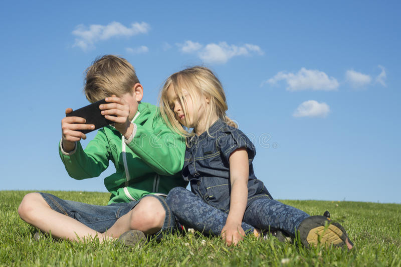 Happy blond children using smartphone (watching movie or playing game) sitting on the grass. stock image
