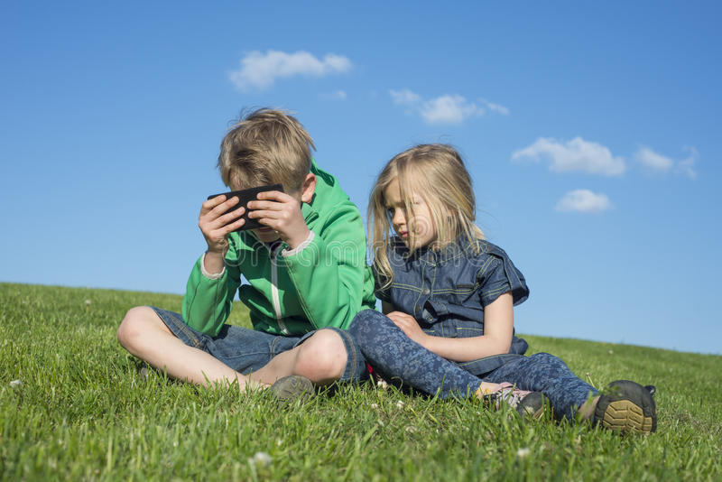 Happy blond children using smartphone (watching movie or playing game) sitting on the grass. royalty free stock images