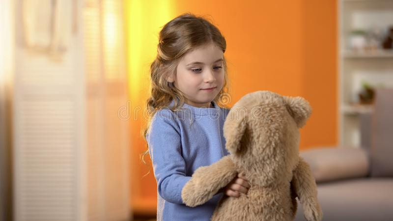 Happy blond curly-haired little girl playing with favorite teddy bear, childhood royalty free stock images