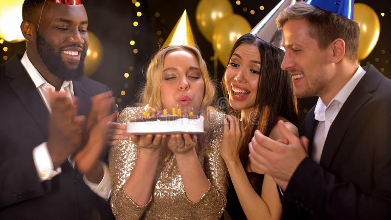 Happy blond female blowing cake candles, friends congratulating woman birthday royalty free stock image