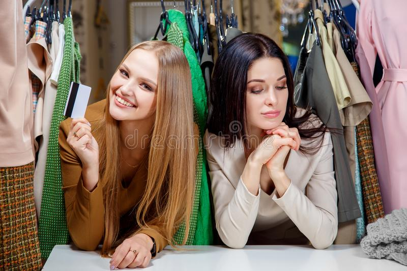 Happy blond girl making shopping with a credit card, but her friend does not have a credit card and sad stock photography