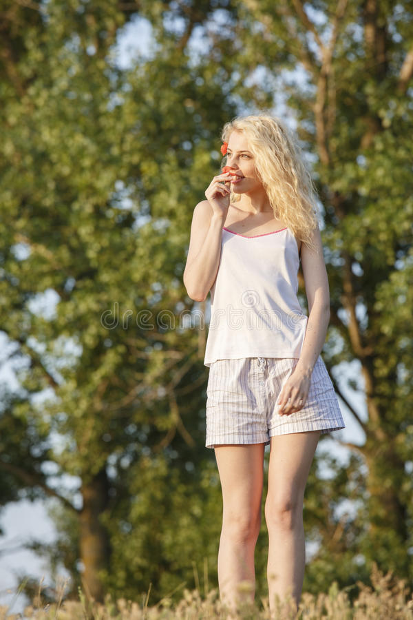 Happy blond girl with poppy flowers stock images