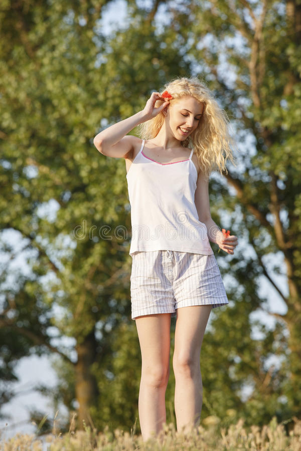 Happy blond girl with poppy flowers stock photos