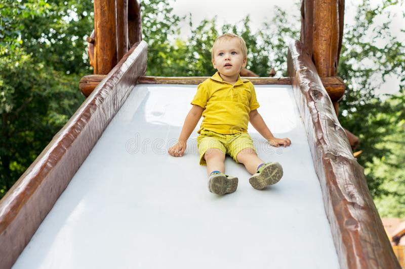 Happy blond kid boy having fun and sliding on outdoor playground. Summer leisure for kids stock image
