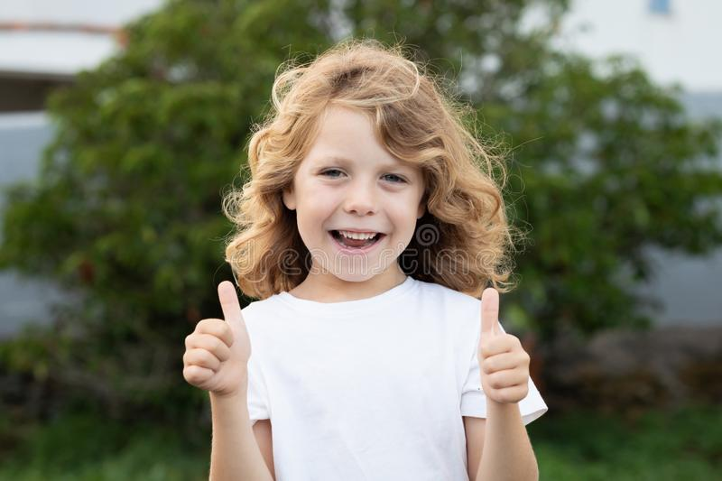 Happy blond kid with long hair saying Ok royalty free stock image