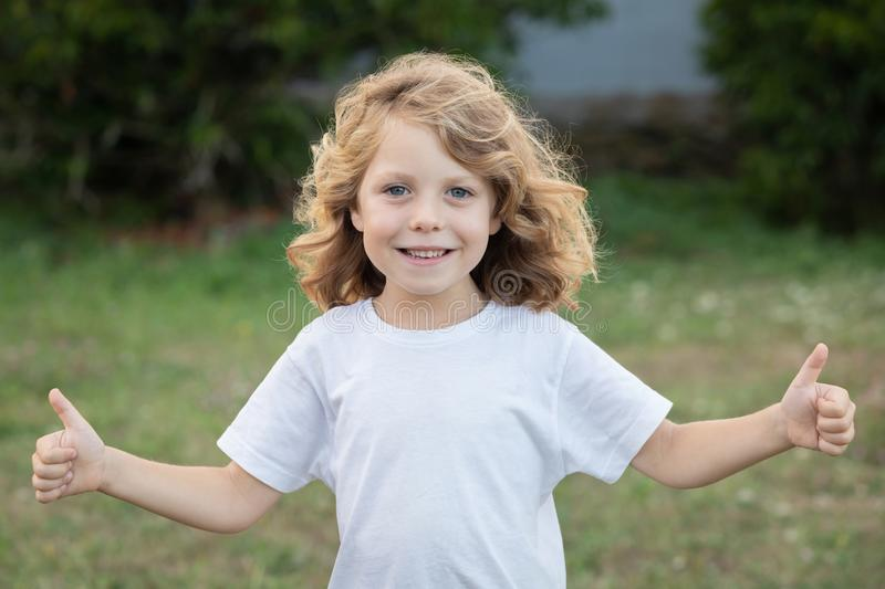 Happy blond kid with long hair saying Ok stock images
