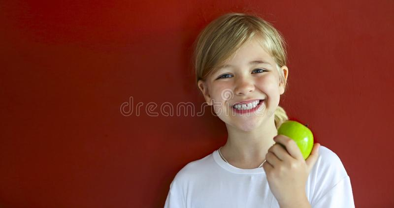 Happy blond little girl with green apple by the red wall stock photo
