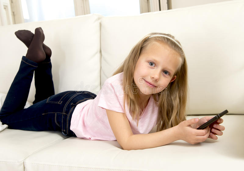 Download Happy Blond Little Girl On Home Sofa Using Internet App On Mobile Phone Stock Photo - Image of hair, couch: 69999468