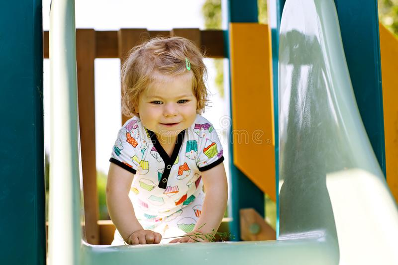 Happy blond little toddler girl having fun and sliding on outdoor playground. Positive funny baby child smiling. royalty free stock photos