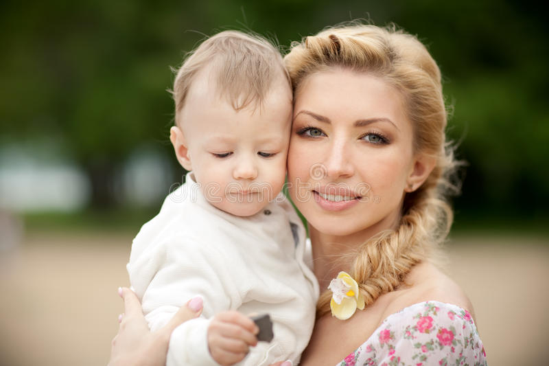 Mother and son. Happy blond mom and one year old son enjoying nature together stock photos
