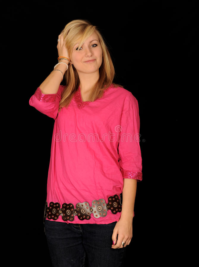 Happy blond teenager. Half body portrait of happy young blond teenager with fashionable pink top; black background royalty free stock image