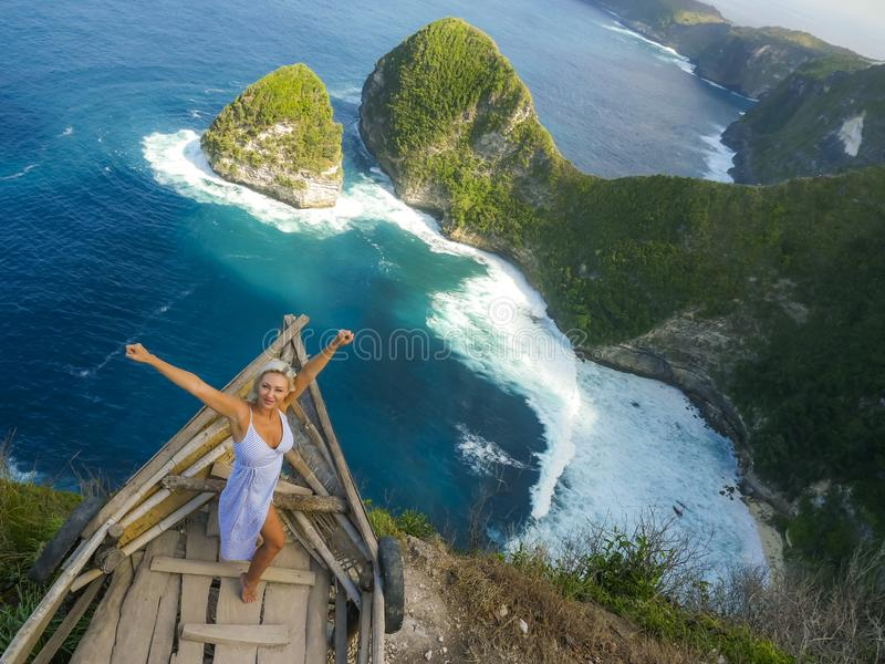 Happy blond tourist woman feeling free on the stunning view of beautiful sea cliff beach at viewpoint enjoying exotic Summer royalty free stock photography