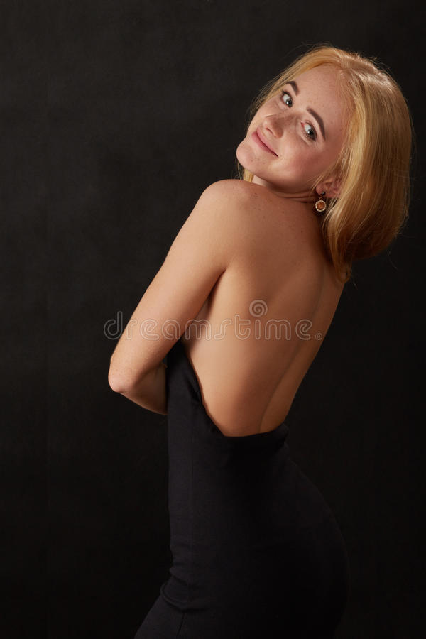 Happy blond woman. With bare shoulders looking back stock image
