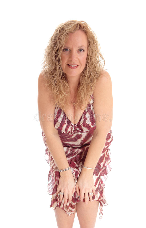 Happy blond woman bending forwards. A image of a happy blond woman standing from the front and bending forwards, smiling, isolated for white background royalty free stock images