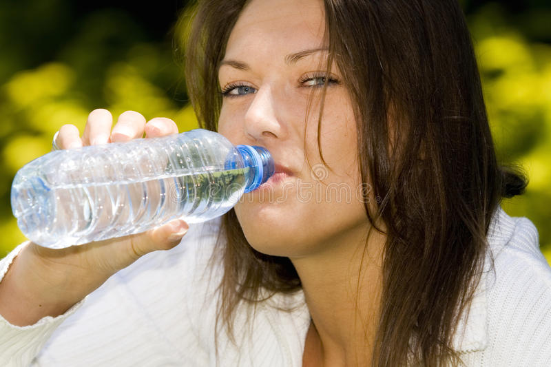 Happy blond woman with a bottle of water stock image