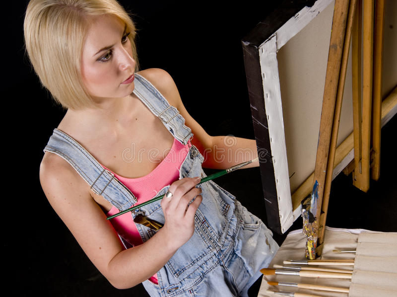 Happy Blond Woman Provides Finishing Touches to Painting on Ease stock photography