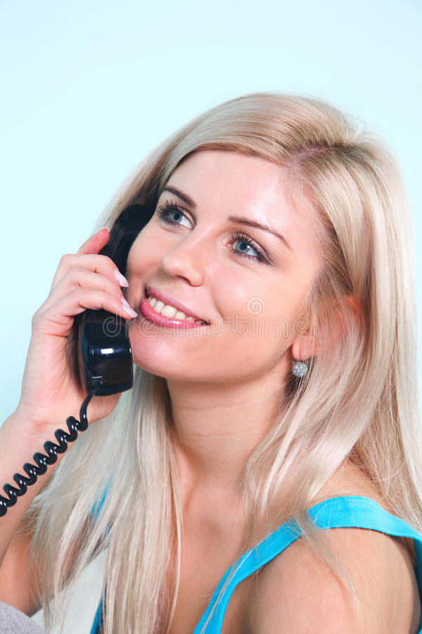 Happy blond woman on the telephone stock photos