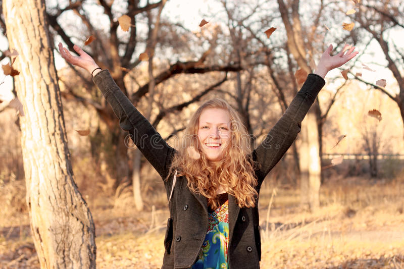 Download Happy Blond Woman Throwing Leaves Stock Image - Image: 22708303