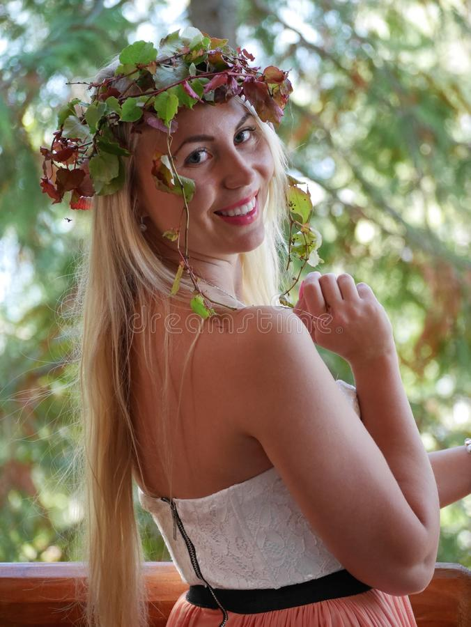 Happy blond woman turning around and smiling with autumn leaves on head. stock images