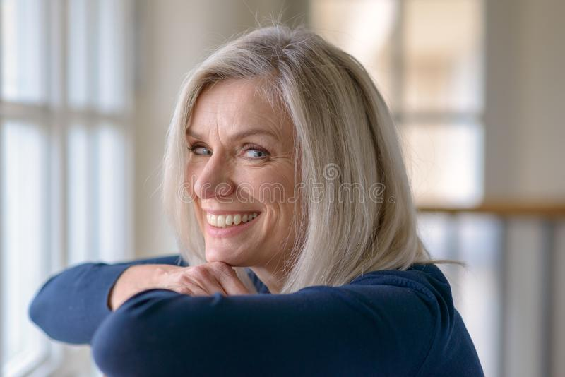 Happy blond woman with a vivacious friendly smile royalty free stock photography