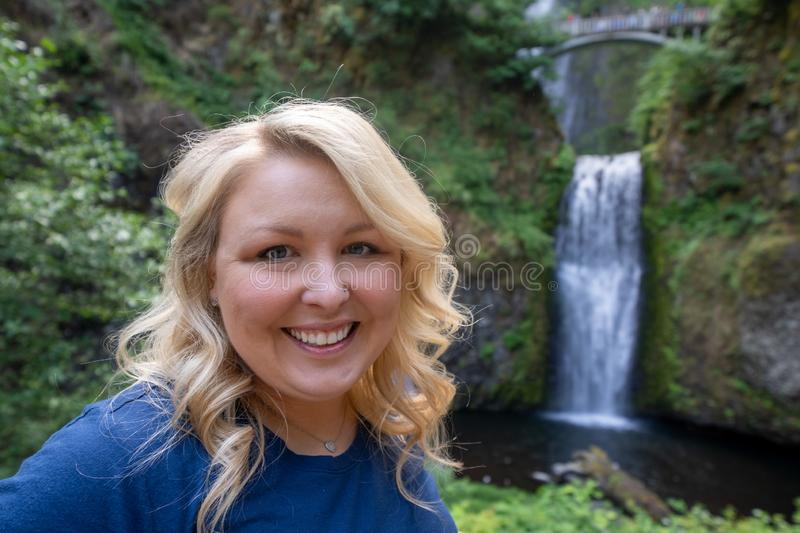 Happy blond woman 30-35 years old poses at Multnomah Falls in Oregon royalty free stock photography
