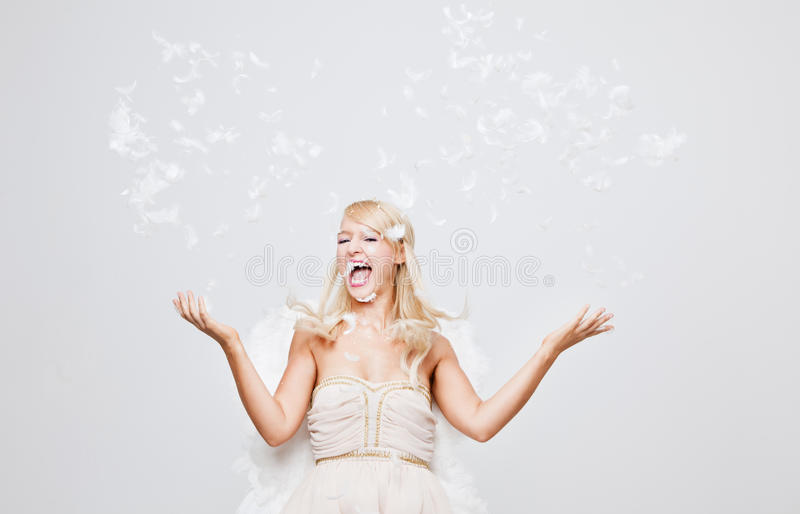 Happy blonde Angel throwing feathers stock image