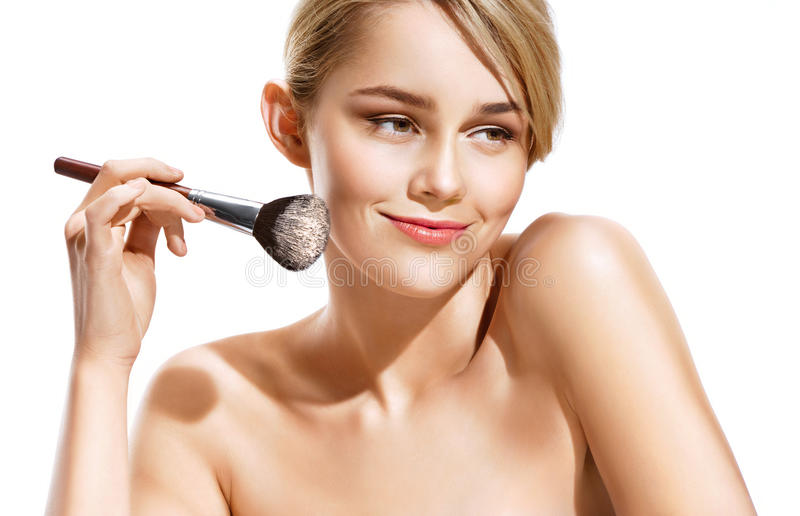 Happy blonde applying dry cosmetic tonal foundation on the face using makeup brush. stock images