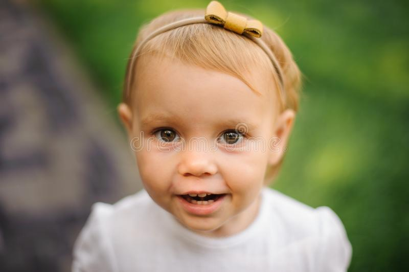 Happy blonde brown-eyed little girl dressed in a white shirt stock images