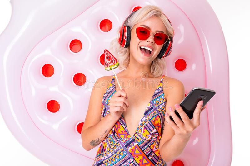 Happy blonde caucasian female stands in swimsuit with big rubber mattress, watermelon lolipop, phone, earphones and royalty free stock photos