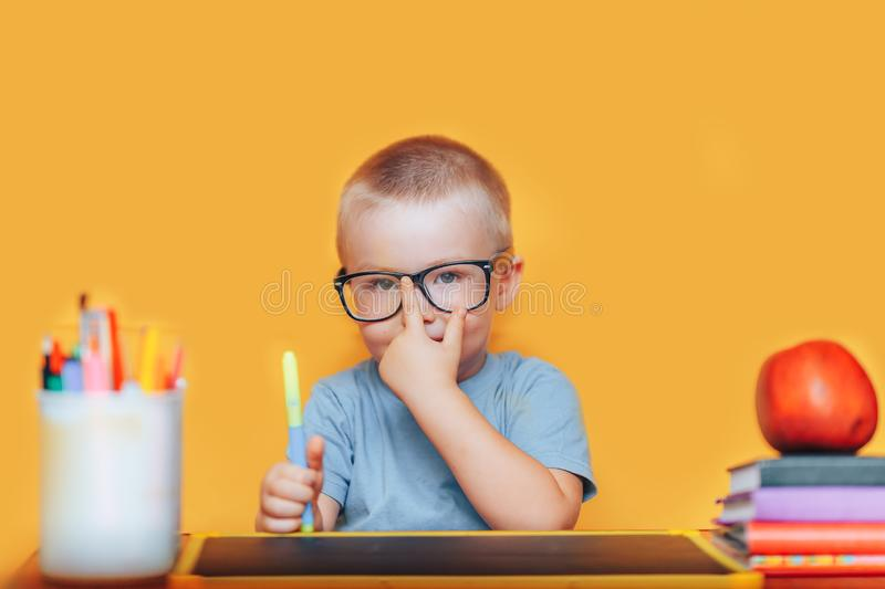Happy blonde clever boy is sitting at a desk in glasses and smiling. Ready for school. Back to school. Apple, pens and books on. Desk royalty free stock images