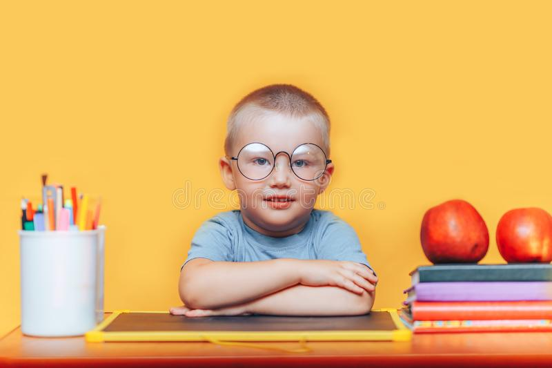 Happy blonde clever boy is sitting at a desk in round glasses and smiling. Ready for school. Back to school. Apple, pens and books. On desk stock photos