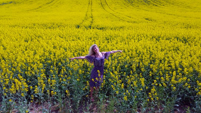 Happy blonde girl on the blooming yellow rapeseed field stock photo